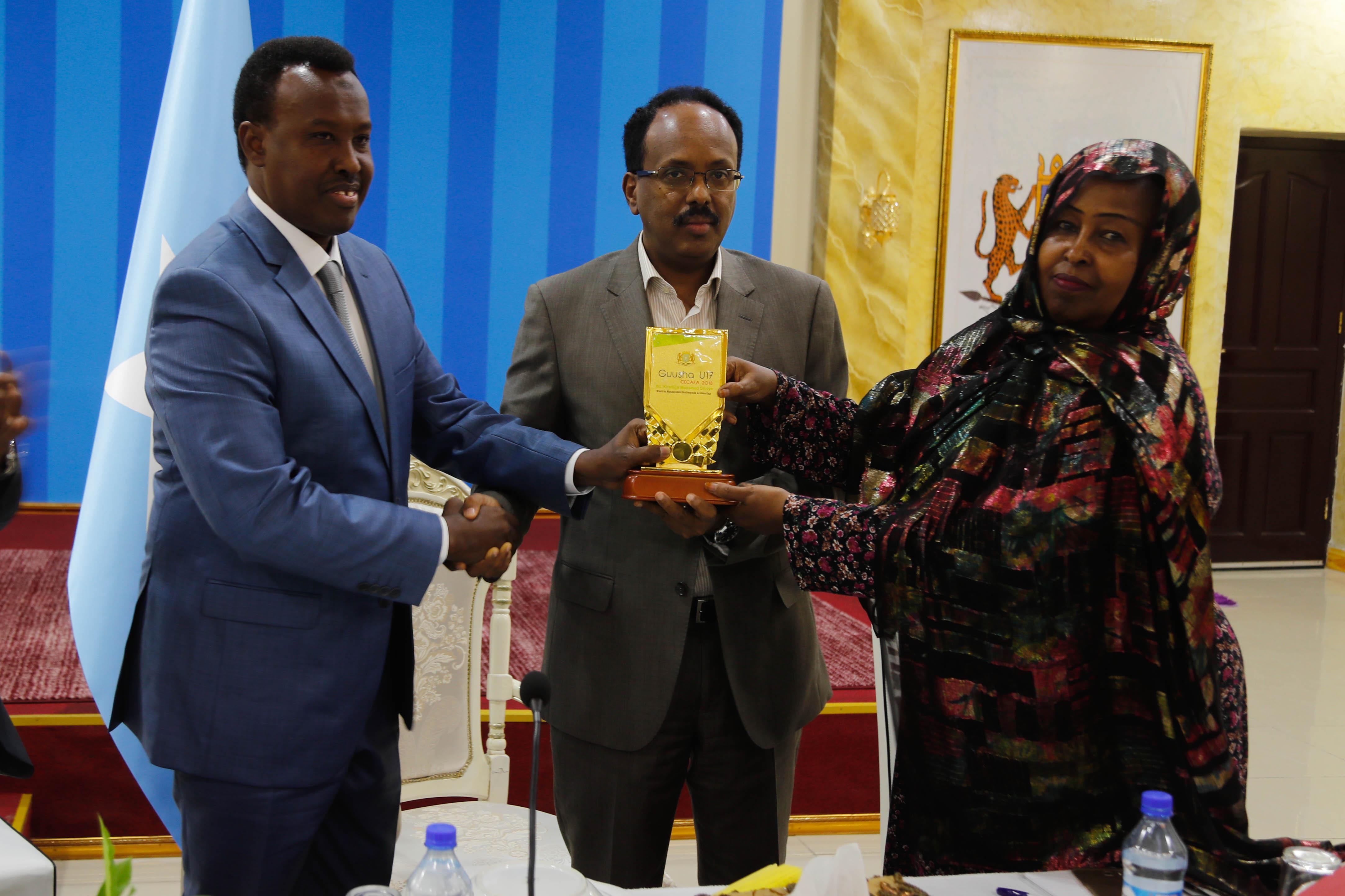 SFF President Abdiqani Said Arab receives the Historic Football Achievement Award from the president of the federal republic of Somalia Mohamed Abdulahi Mohamed as minister of sport Hon. Khadija Mohamed Diriye is pictured on the