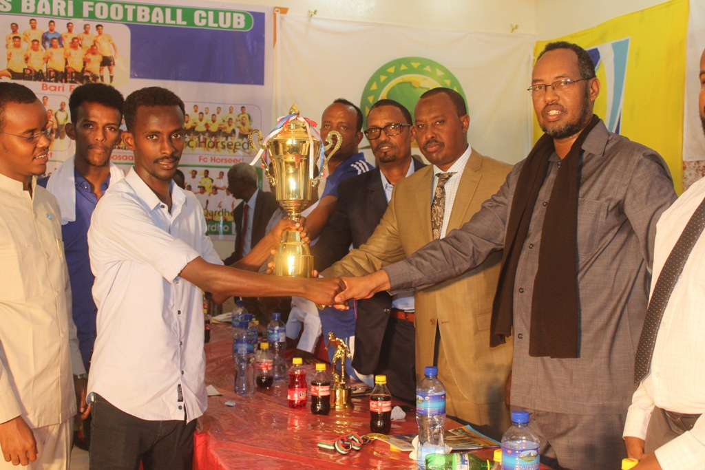 Bari Football Club Captain Abdiqani Yusuf Abshir receives the trophy from the minister for youth and sport of the Puntland State of Somalia, Abdirahman Sheik Ahmed