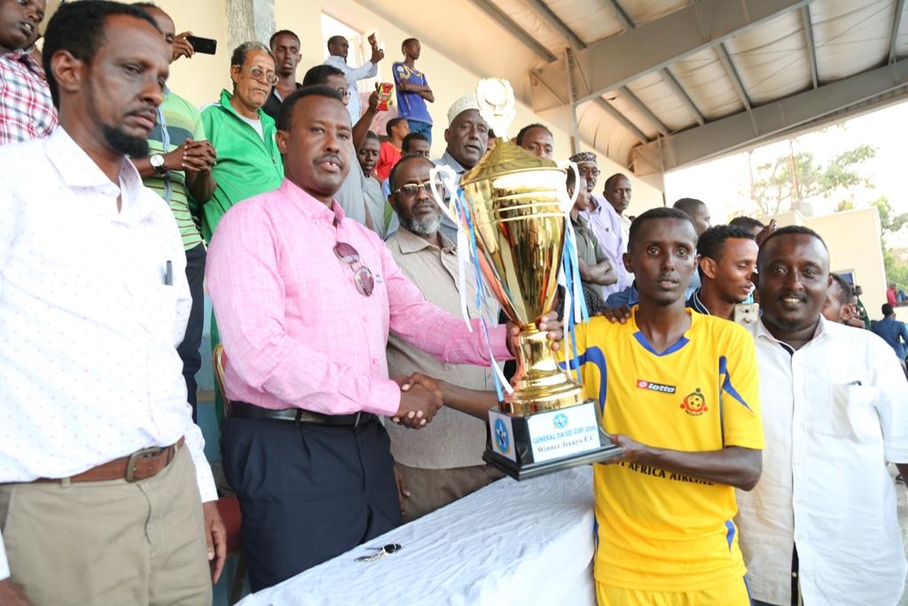 SFF president Abdiqani Said Arab, presents the trophy to Jeenyo FC captain Ahmed Tahliil Ali