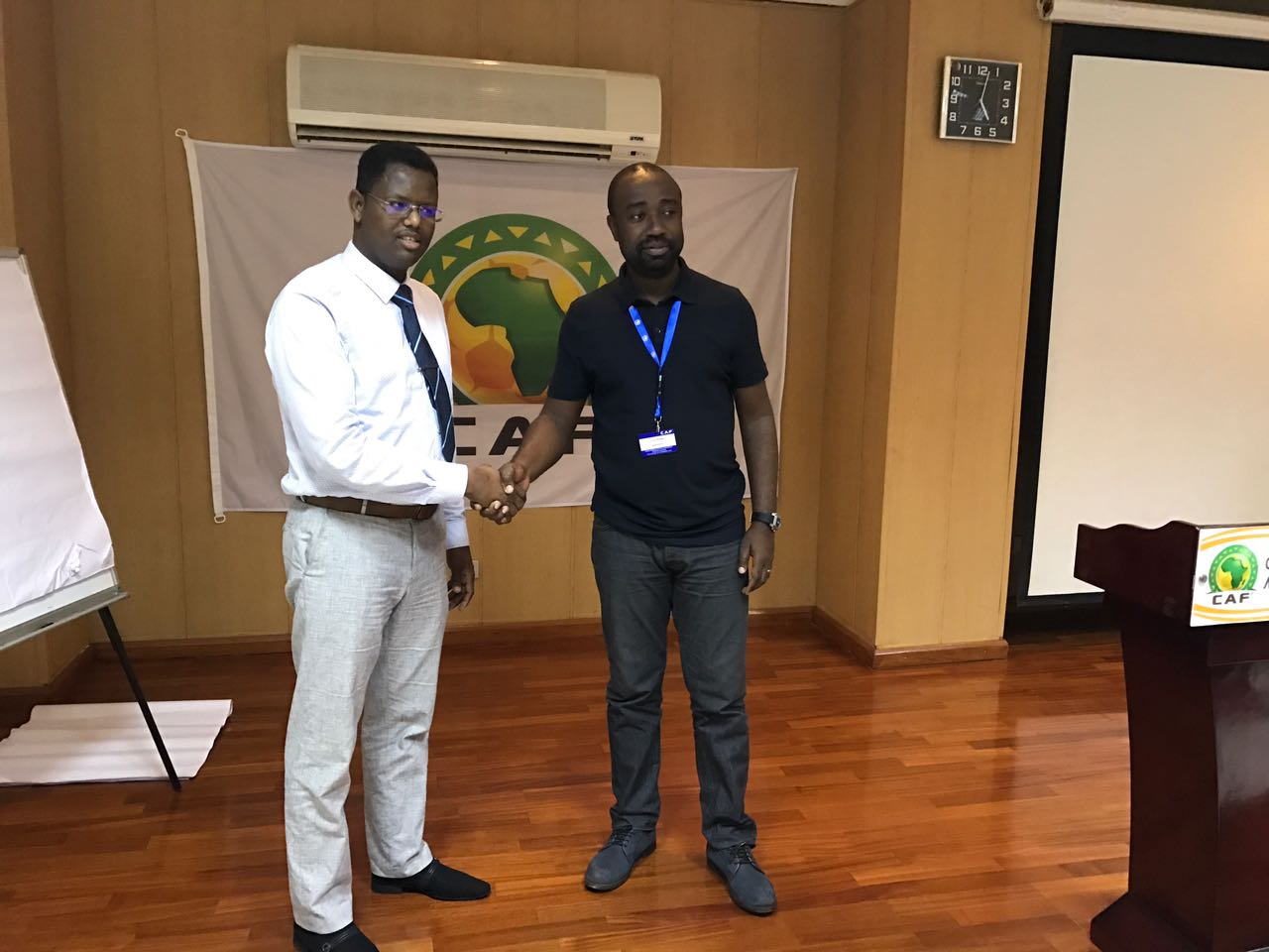 CAF head of Media Junior Binyam right shakes hands with  Somali FA director of communication Shafi'i Mohyaddin Abokar at CAf Centre of excellence in Cameroon